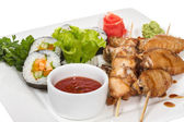 Buffalo chicken wings on plate with sushi — Stock Photo