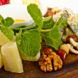 Various types of cheese with honey, nuts and grapes on plate, is — Стоковая фотография