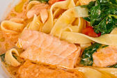 Tasty pasta with cream, salmon, cheese and parsley close up — Stock Photo