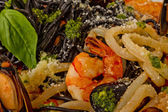 Black tagliatelle (pasta made with cuttlefish ink) with shrumps, — Stock Photo