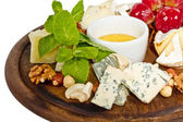 Various types of cheese with honey, nuts and grapes on plate, is — Stock Photo