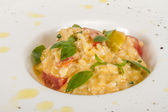 Photo of delicious risotto dish with herbs and tomato on white b — Stock Photo