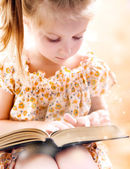 Little girl reading book — Stok fotoğraf