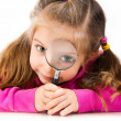 Girl looking through a magnifying glass — Foto Stock