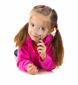 Girl looking through a magnifying glass — Stock Photo