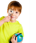 Boy looking through a magnifying glass — Stock Photo