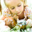 Stock Photo: Little girl with magnifying glass looks at flower