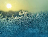 Ijs patronen en zon op winter glas — Stockfoto