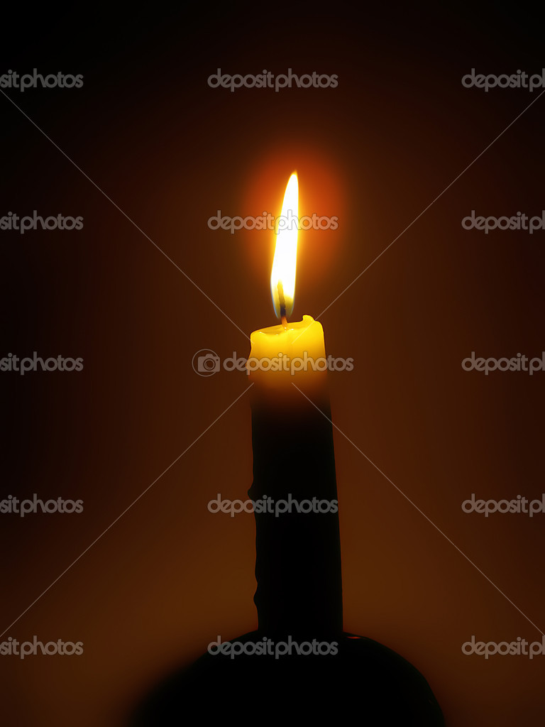 Bright burning candle in the dark  Stockfoto #9854505
