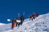 Group of climbers with skis and snowboards — Stock fotografie