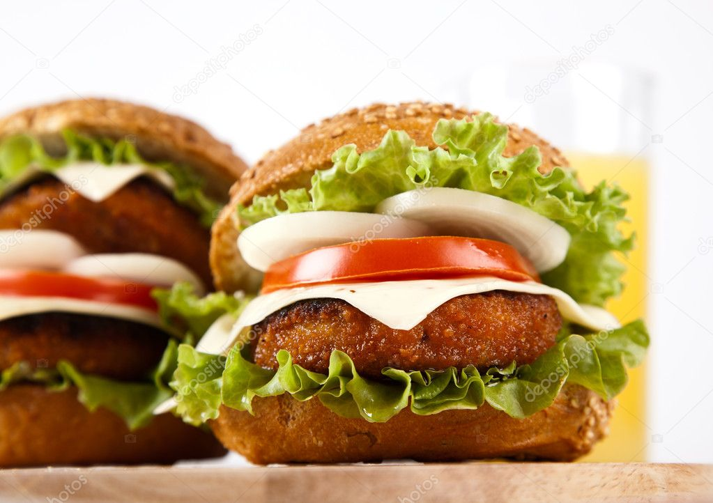 Hamburger with fish cutlet and vegetables on wooden board on white background — Stock Photo #10572123