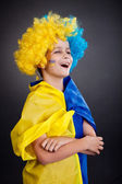 Football fan with ukrainian flag on a black background — 图库照片