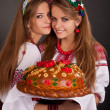 Young women in ukrainian clothes, with garland and round loaf on - Stock Photo