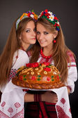 Young women in ukrainian clothes, with garland and round loaf on — Stock Photo