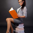 Cute mixed race student girl reading while sitting on heap of bo — Stock Photo