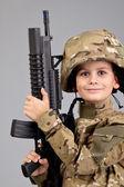 Młody chłopak ubrany jak żołnierz z karabin — Zdjęcie stockowe