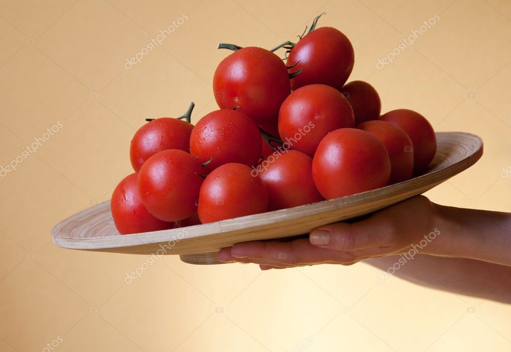 Woman's hands holding a round bamboo plate with bunches of fresh tomatoes on a yellow background — Stock Photo #10075532
