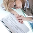 Lying tired next to laptop — Stockfoto