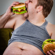 Stock Photo: Fat man eating hamburger