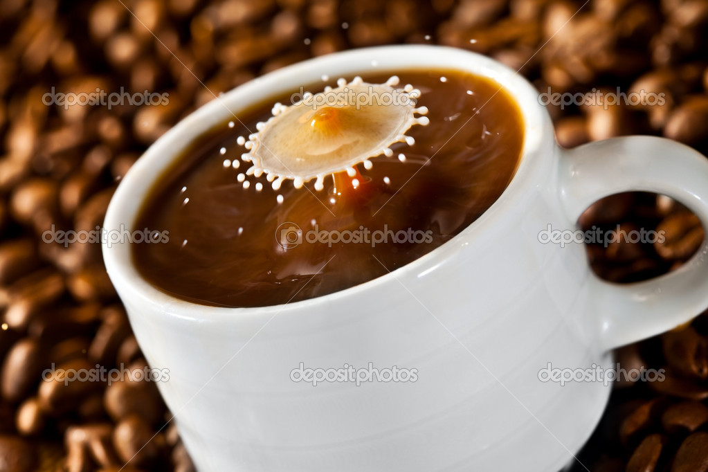 Milk drop falling into a cup of coffee — Stock Photo #8515303