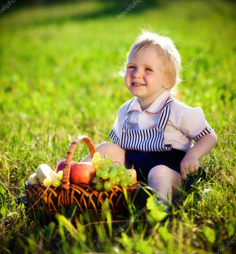Little boy with a basket of fruit sits on a grass — Stock Photo #9334827