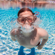 Teenager floats in pool - Stockfoto