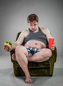 Fat man eating hamburger — Stock Photo