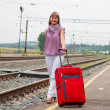 Woman with luggage waiting train on railroad — Stock Photo #10057410