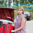 Blonde woman packing her baggage into the car — Stock Photo