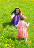 Young mum with a small daughter play to a glade with dandelions — Stock Photo
