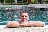 Tropikal otel havuzunda olgun gülen adam — Stok fotoğraf