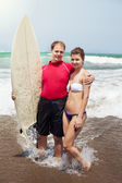 Man embraces the girl and holds surf — Stock Photo