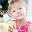 Fair-haired girl in a pink dress with a New Year's gift at a fur-tree — Stockfoto