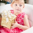 Fair-haired girl in a pink dress with a New Year's gift at a fur-tree — Stok fotoğraf