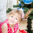 Red gift in hands of the fair-haired girl which sits near to a fur-tree — Stock Photo