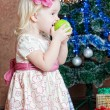 Little girl at a Christmas fir-tree - Stock Photo
