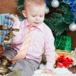 Little boy in a room sits at a Christmas fur-tree and calls by phone — Stock Photo
