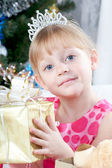Holka v růžových šatech s novoroční dárek v srsti strom — Stock fotografie