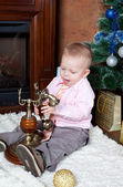 在一个房间里的小男孩坐在一棵圣诞树毛皮-并调用通过电话 — 图库照片