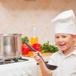 Stock Photo: Little boy on kitchen helps to make a dinner