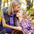 Happy mum and the daughter play autumn park on the fallen down foliage — Stock Photo