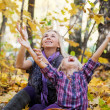 Happy mum and the daughter play autumn park on the fallen down foliage — Stock Photo #8739741