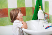 Little girl washes in a bathroom — Stock Photo