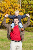 Small son sits on shoulders at the father. — Stock Photo