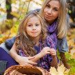 Stock Photo: Happy mum and the daughter play autumn park