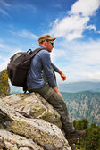 Man - tourist sits on a rock and admires a mountain landscape — Stock Photo