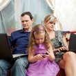 Family of three sits on a sofa, everyone with the personal computer - Stock Photo