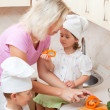 Mum with children prepares for vegetable salad on kitchen — Stock Photo
