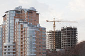 Building elevating crane on a background of a under construction multi-storey house — Stock Photo