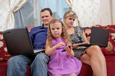 Parents and the child have a rest on a sofa, everyone with the personal computer — Stock Photo
